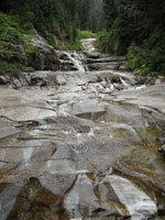 Water cascades across rock slabs at Denny Creek.