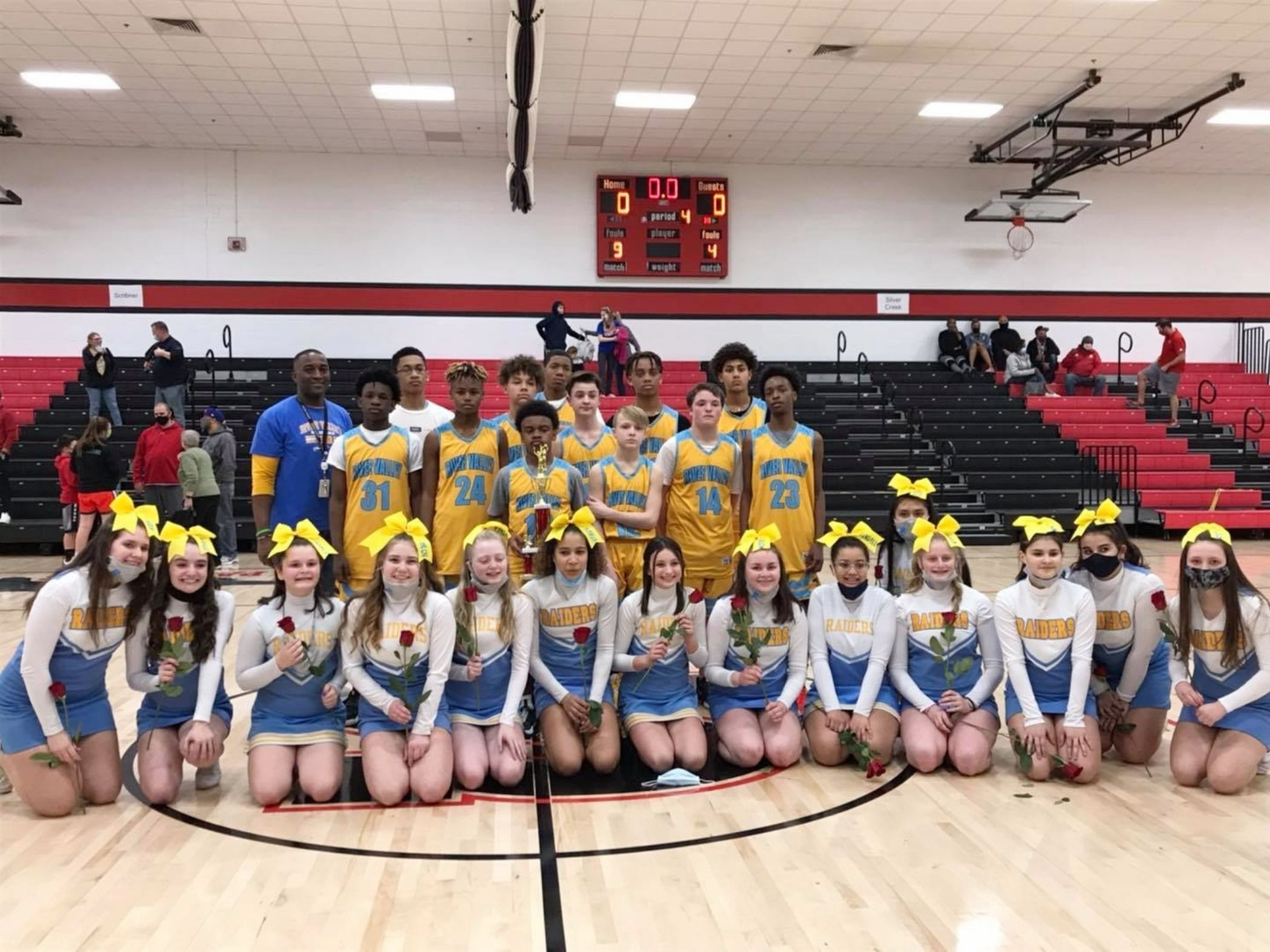 Basketball team and cheerleaders pose for photo