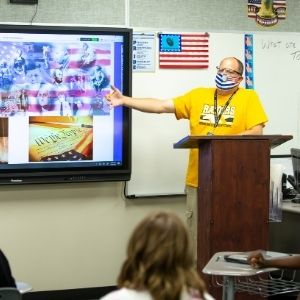 Teacher points to whiteboard