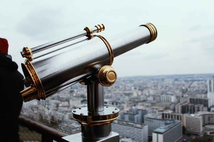 selective focus photography of gray and gold colored telescope