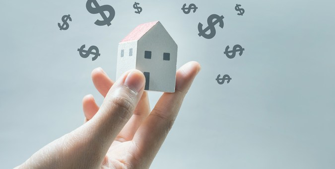 House model on human hands with dollar icon.Savings money and real estate concept