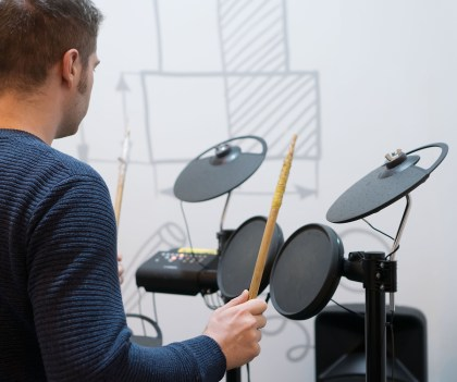 Man playing on electronic drums. Back view.