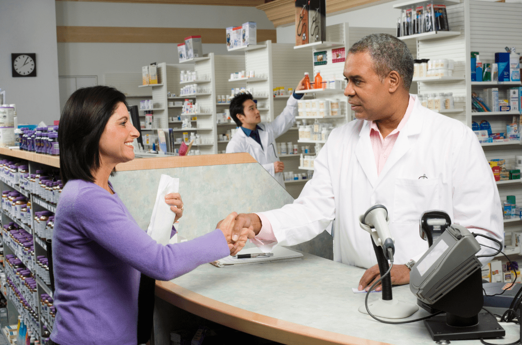 Pharmacist shaking hands with a happy and satisfied patient