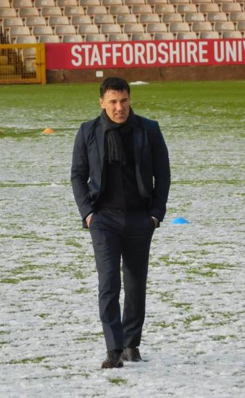 Dean Saunders inspects the snow-covered pitch