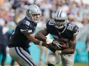 Dallas Cowboys quarterback Tony Romo (9) hands the ball to running back Darren McFadden.