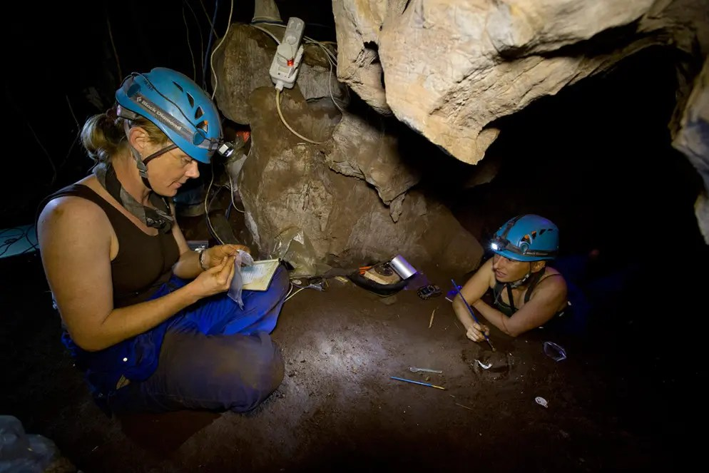 """Underground astronauts"" Marina Elliott (right) and Becca Peixotto (left) work inside the cave where fossils of H. naledi, a new species of human relative, were discovered. The find was announced by the University of the Witwatersrand, the National Geographic Society and the South African National Research Foundation and published in the journal eLife. Photograph by Garrreth Bird."