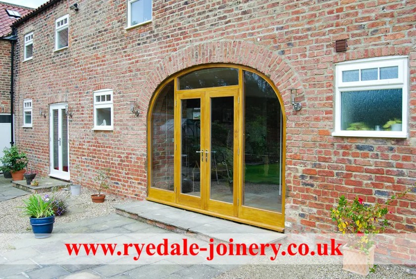 An image of a large bespoke window with a curved top. The window is installed in a farm barn conversion.