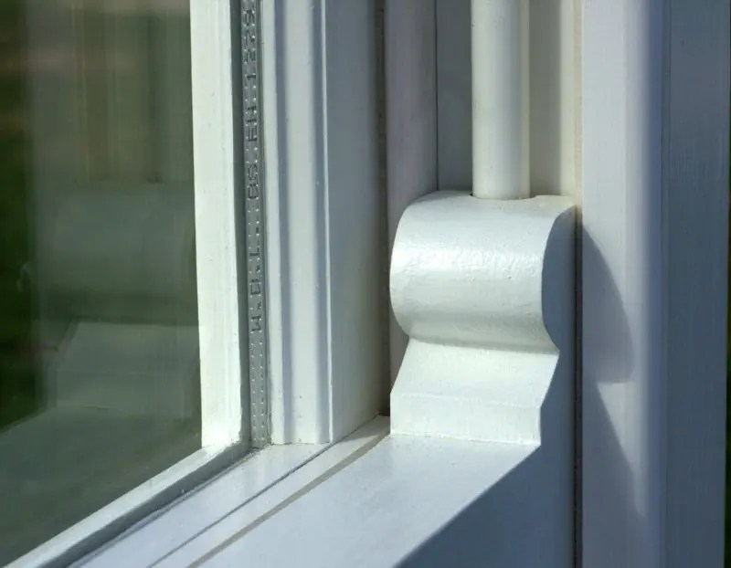 A close-up image of the lower right corner of a sash window