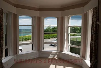 A photograph of a refurbished and double glazed bay sash window taken from inside the building looking outside.
