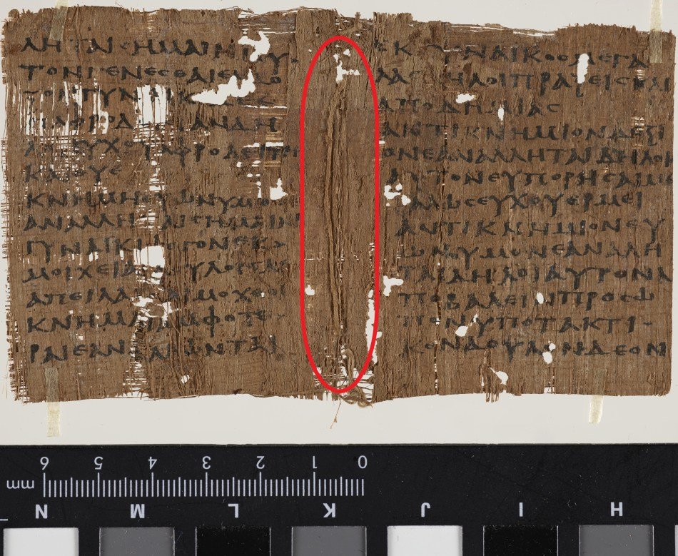 Page of papyrus with sewing remnants in the centre where it was folded