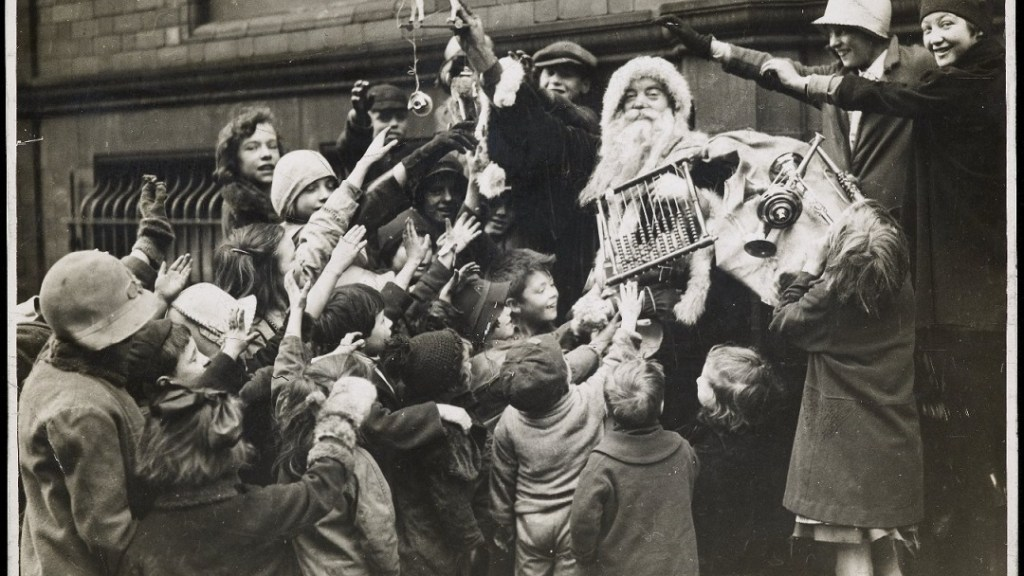 children on Wood Street surrounding man dressed as Father Christmas handing out toys