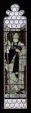 Stained glass portrait of Bishop Augustine of Hippo, wearing religious robes, Mitre and holding a staff.