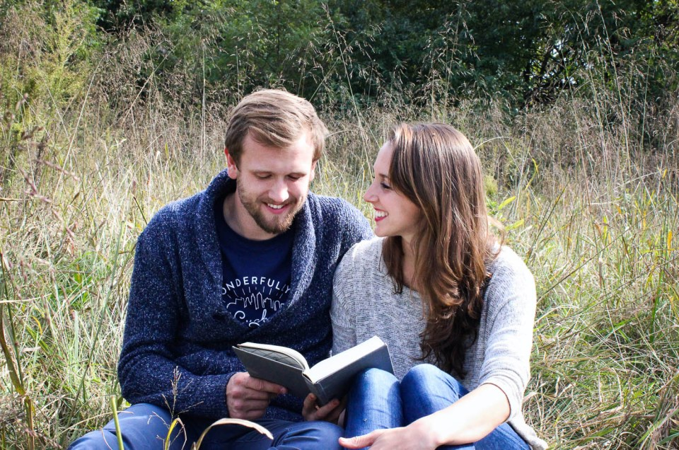 Couple sitting in field reading a book