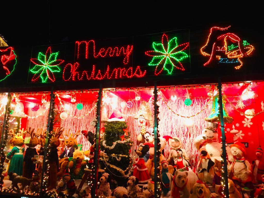 Vers une désacralisation de la fête de Noël en Haïti - A group of people on a stage in front of a store - Christmas lights