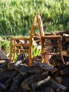 Deux chaises en bois, dos à dos, dans la nature