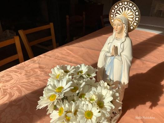 Statuette de la Vierge Marie près d'un bouquet de fleurs