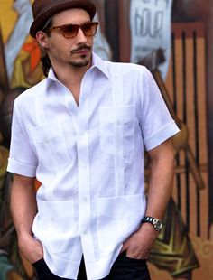 Light-skinned Hispanic man wearing white guayabera in the Cuban style, sunglasses, and a hat.  He has a mustache, a goatee, and a soul patch, a classic Cuban facial hair pattern.