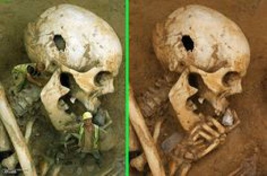 """Fake - Giant Skull - The real image is on the right. """"Cliffs End - skull"""" Late Bronze Age burial of an elderly man. He was found at the bottom of a burial containing 12 complete skeletons and other human bone. He seems to be holding a small piece of chalk, which does not occur naturally on this site. The man had met a violent death, from multiple wounds to the head."""