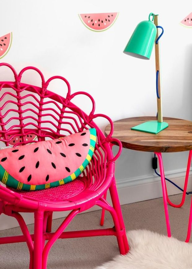 A+wicker+chair+painted+in+punchy+hot+pink+and+a+mint-green+table+lamp+follow+the+watermelon+theme+of+the+wall+print+and+throw+pillow.: