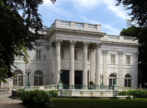 """Marble House is a Gilded Age mansion in Newport, Rhode Island, now open to the public as a museum run by the Newport Preservation Society. It was designed by the society architect Richard Morris Hunt. The mansion was built as a summer """"cottage"""" retreat between 1888 and 1892 for Alva and William Kissam Vanderbilt. The fifty-room mansion required a staff of 36 servants, including butlers, maids, coachmen, and footmen.:"""