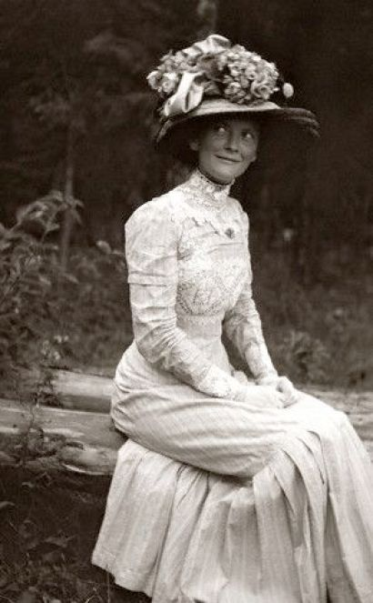 June 1900 - I love love love this picture so much. From the amazing inlaid lace work, to the piles of things on her hat, right down to the humorous look on her face!: