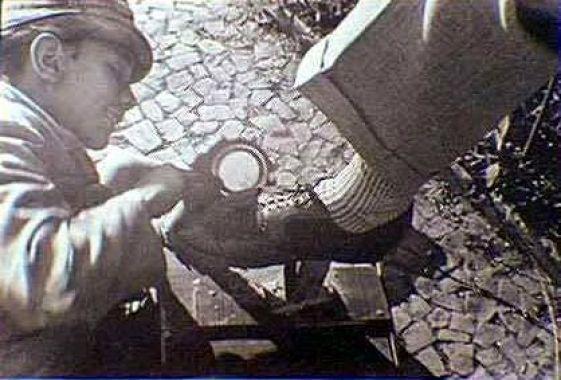 """1939 - Engraxate no centro da cidade. Essa honrada profissão muito comum na São Paulo de antigamente, quando a ordem era andar sempre garboso, mereceu uma obra de arte de autoria do italiano Ricardo Cipicchia (1885/1969). Trata-se de um monumento chamado de """"Contando a Féria"""", que presta homenagem aos engraxates e jornaleiros.:"""