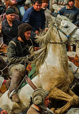 "Buzkashi match in Afghanistan. Buzkashi (literally ""goat dragging"" in Persian) or kokpar is the Central Asian sport in which horse-mounted players attempt to drag a goat or calf carcass toward a goal. It is the national sport of Afghanistan, although it was banned under the Taliban regime.:"