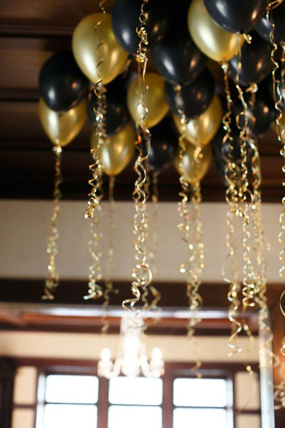 8 incredible New Year's Eve Party Decoration Ideas - black and gold balloons with gold ribbon: