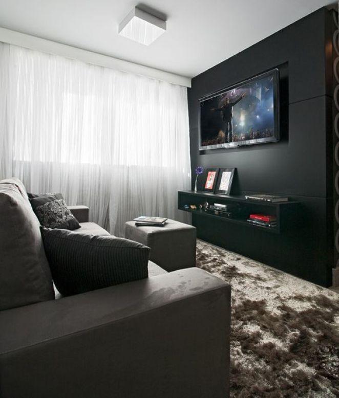 O Home theater de parede preta e móveis em tons de cinza é aconchegante, sofisticado e masculino: