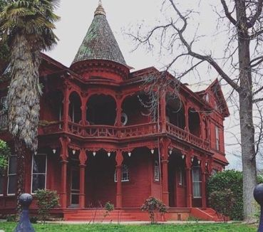 Gothic Victorian mansion. Painting a Queen Anne in one color obscures the details, whether it is white or red. Colors don't have to be bright to enhance the architecture.:
