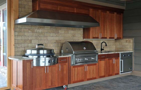 outdoor kitchen with lynx professional grill gorgeous wood panel cabinets large vent hood and a on outdoor kitchen ventilation id=63537