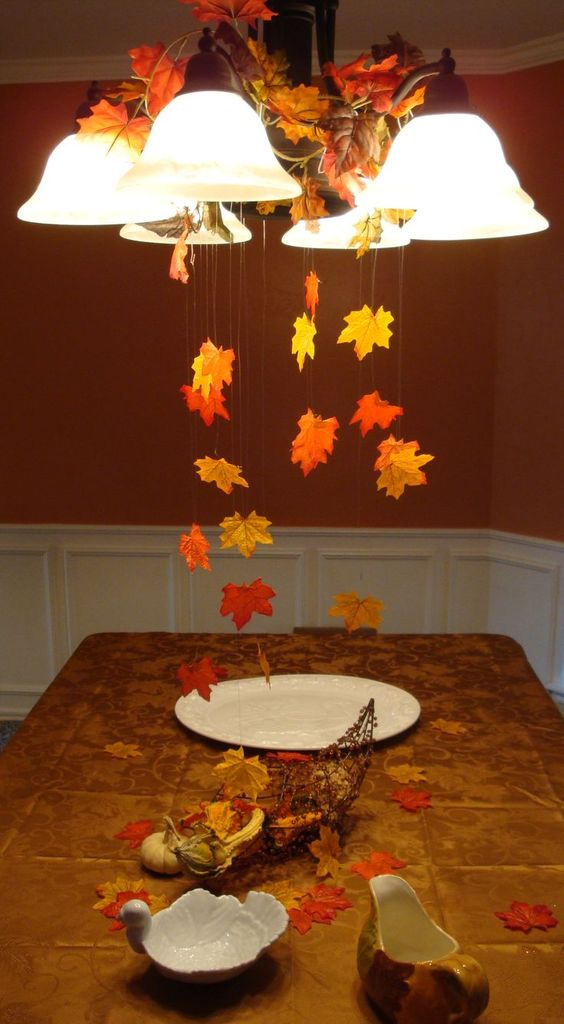Using fishing line and a bag of leaves from from the dollar store I created a fall scene for my Thanksgiving table! Hung from the light with colored paper clips to blend in! Spread out excess leaves on the table:
