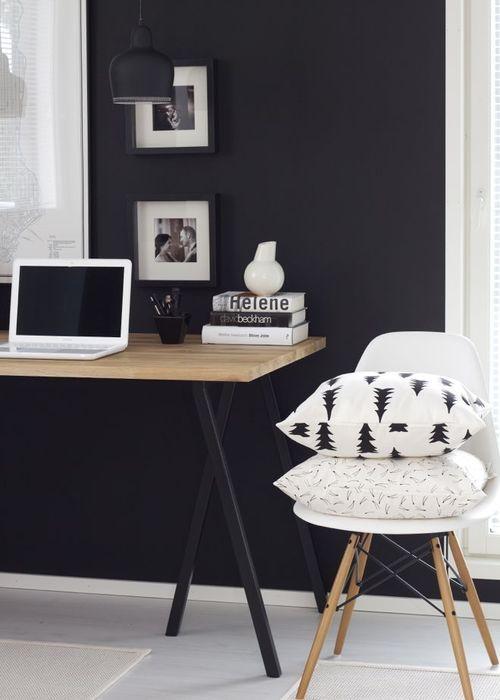 parede pintada de preto, decoração de home office com parede preta e mesa com pés de cavalete em preto e tampo aem madeira: