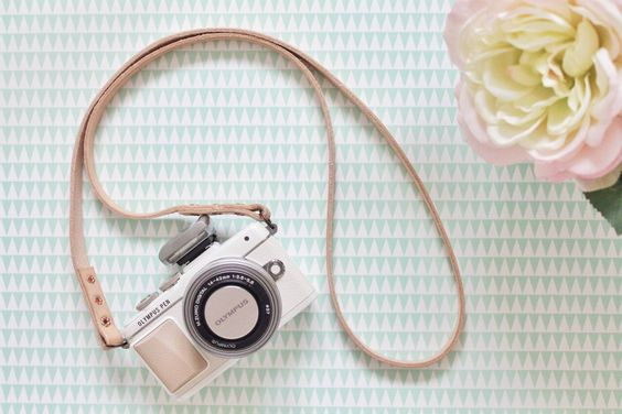 Vintage style blogger desk with Olympus Pen camera and flowers