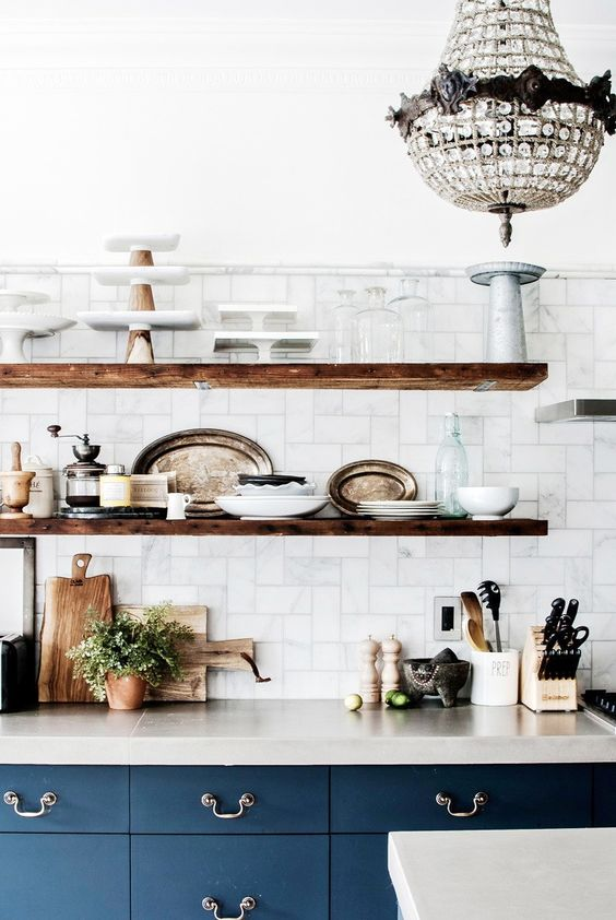 Love these bold blue cabinets, unique tiling on the walls and raw wood floating shelves in this kitchen. via @MyDomaine: