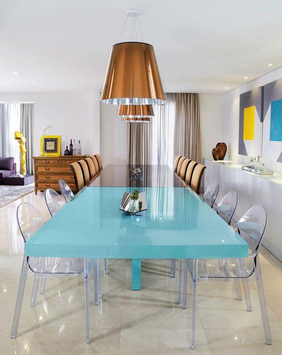 Clássico com Moderno... Um charme...A sala de jantar e a copa são integradas e o que diferencia os dois ambientes é a cor da mesa e o estilo das cadeiras. Na copa, a mesa é em laca azul-turquesa e as cadeiras são de acrílico transparente. Na sala de jantar, a mesa tem tampo em vidro espelhado bronze e cadeiras de madeira com estofado em tecido nude. Gosto da proposta de integrar os ambientes e diferenciar pelos acabamentos.: