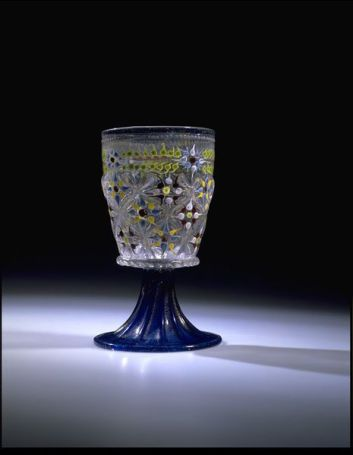 Goblet, Italy (Venice), ca 1475-1510, Coulourless and clear blue glass, blown in a dip-mould and tooled, gilt and enameled. The staple production of medieval and early Renaissance glassmakers was beakers and bottles. This splendid beaker on a high foot was made in Venice by the famous glass-blowers on the island of Murano. The decoration in gold leaf and painted enamels was applied after the piece had been shaped and gradually cooled...: