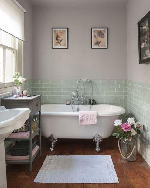 Um clima vintage e romântico invade esse banheiro, onde os olhos logo se voltam para a relaxante banheira de estilo vitoriano com pés prateados. As flores e os quadros arrematam a decoração de um jeito simples e acolhedor.: