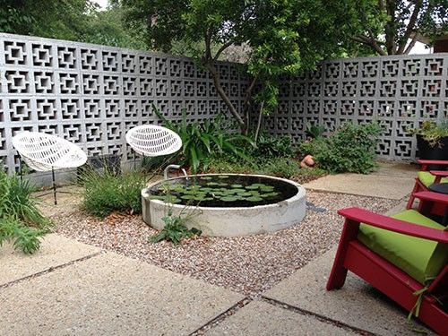 Water garden in concrete tunnel.   Bamboo planted in steel culverts along fence for screening w/o growing out of control.  Redenta's Garden - organic gardening products modern landscape design landscaping plants flowers Dallas Arlington Fort Worth