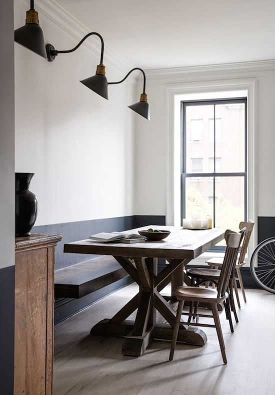 two toned wall, charcoal gray wall on bottom, white on top, farmhouse table, gooseneck lamp:
