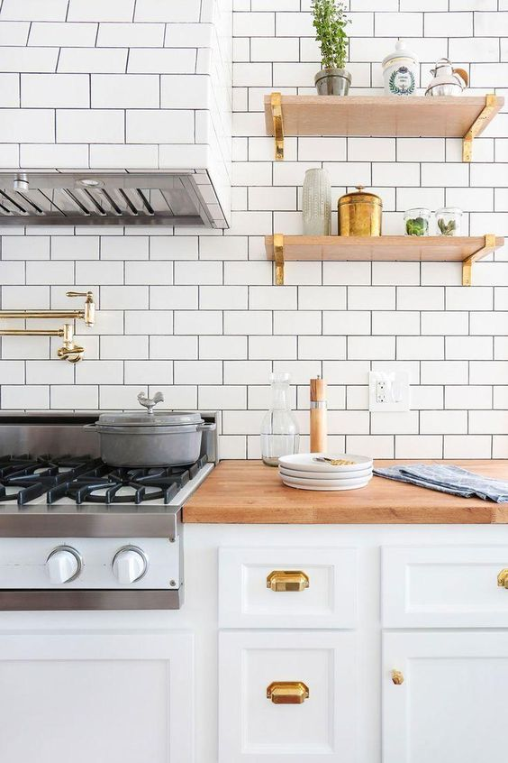 Bright new kitchen remodel with white millwork cabinets, brass drawer pulls and handles, brass brackets under the open shelving, butcher block counter tops and white subway tile with dark gray grout on the walls, backsplash and on the oven range hood.: