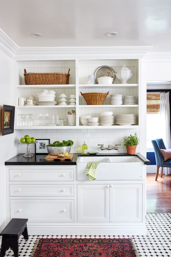 Wicker baskets, greenery, and a richly hued mat prevent the sink and shelving area in this tiny kitchen from feeling too white.:
