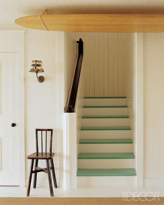 Designer Kerry Joyce painted the steps of a staircase in playful ocean-green Bezique by Pratt & Lambert Paints for an actress's family home in Malibu, California. The sconce and surfboard tied to the ceiling reiterate the home's lighthearted, seaside vibe.