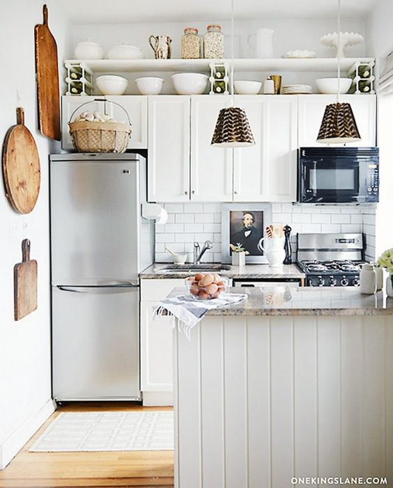 Kitschy country accessories give this compact kitchen an eclectic pastoral vibe, but the foundations of it—subway tile, granite counters, and white beadboard.:
