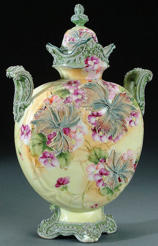 A NIPPON MORIAGE DECORATED PORCELAIN COVERED URN CIRCA 1915 WITH LARGE MORIAGE GRAPE LEAVES ON A PAINTED WILD FLOWER GROUND WITH TWO HANDLES: