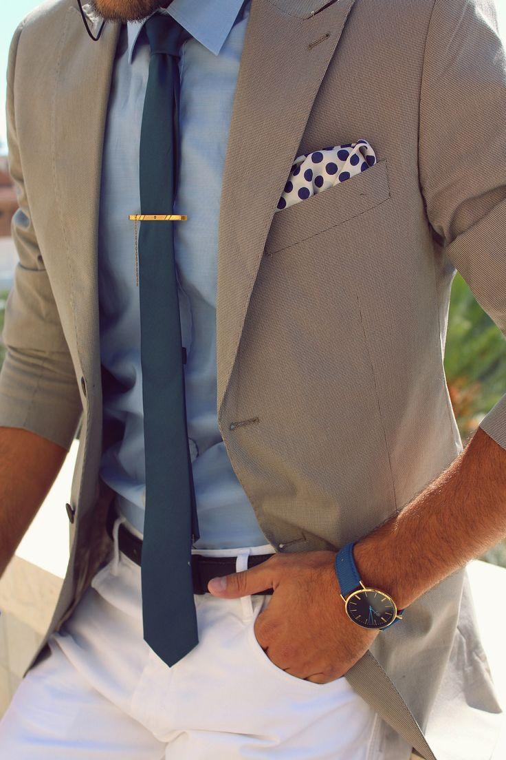 tan blazer. light blue oxford. light khaki pants. navy tie. white pocket square w/blue dots. watch. gold tie bar. brown leather