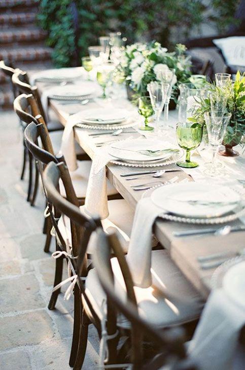 sillas de madera casuales puntuadas con cojines blancos yuxtaponen cargadores elegantes y cubiertos de plata .: