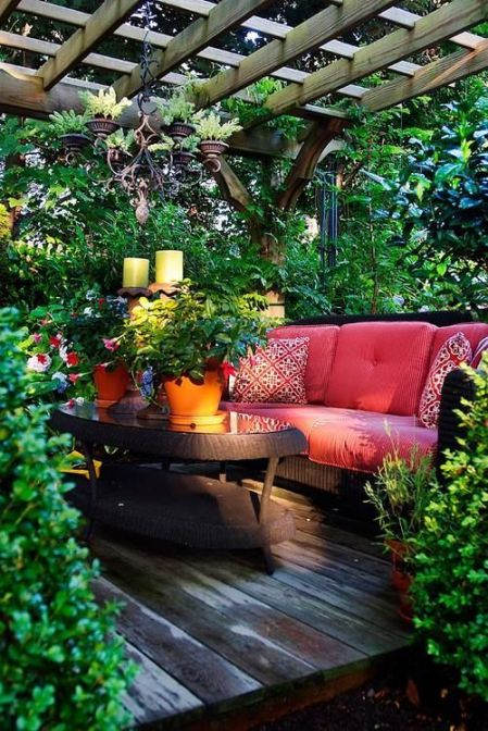 Outdoor Space under a pergola. Sitting area, surrounded by greenery, on a wooden deck.: