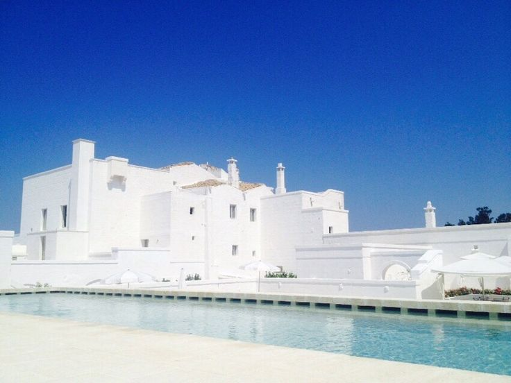 Exterior shot of Masseria Le Carrube in Puglia, Italy with blue sky and gorgeous blue water