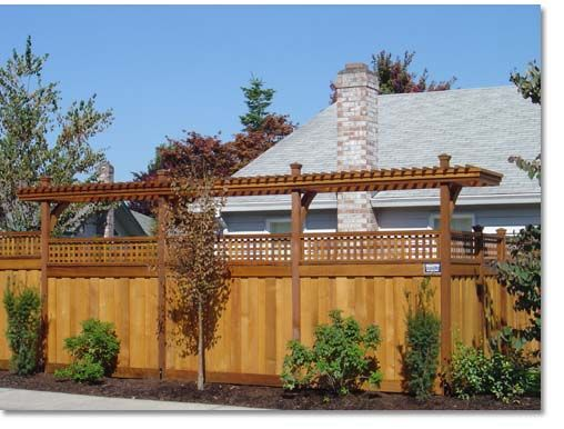 Wooden Privacy Fence With A Tall Arbor For Added Screening